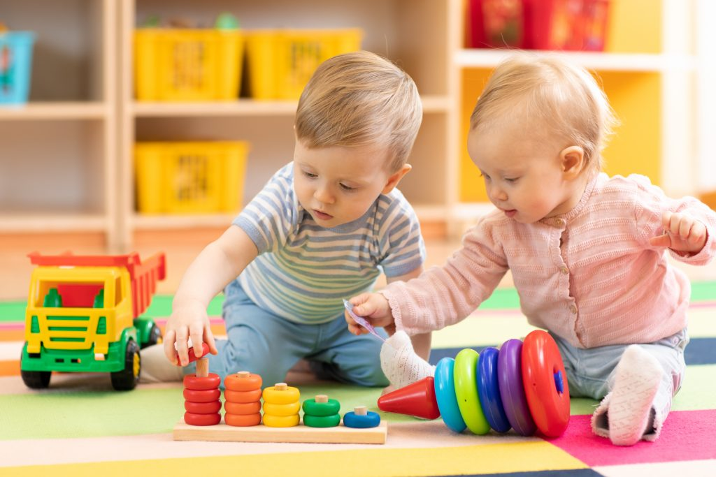 Close-up of a baby boy and girl playing with toys together on the floor