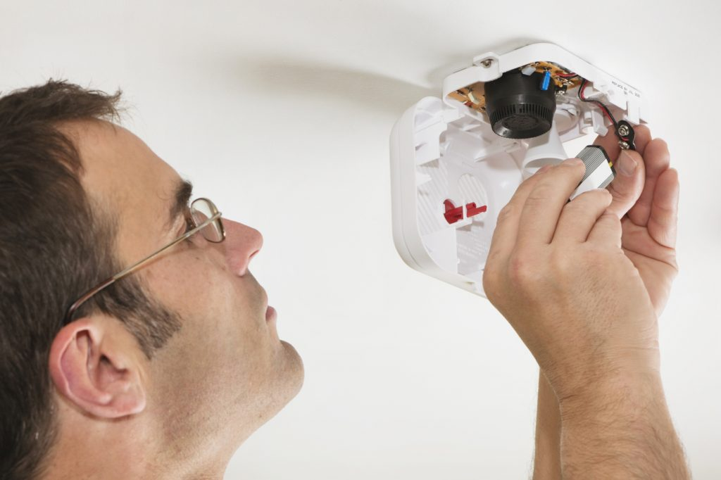Close-up of an adult male replacing the batteries in a smoke detector