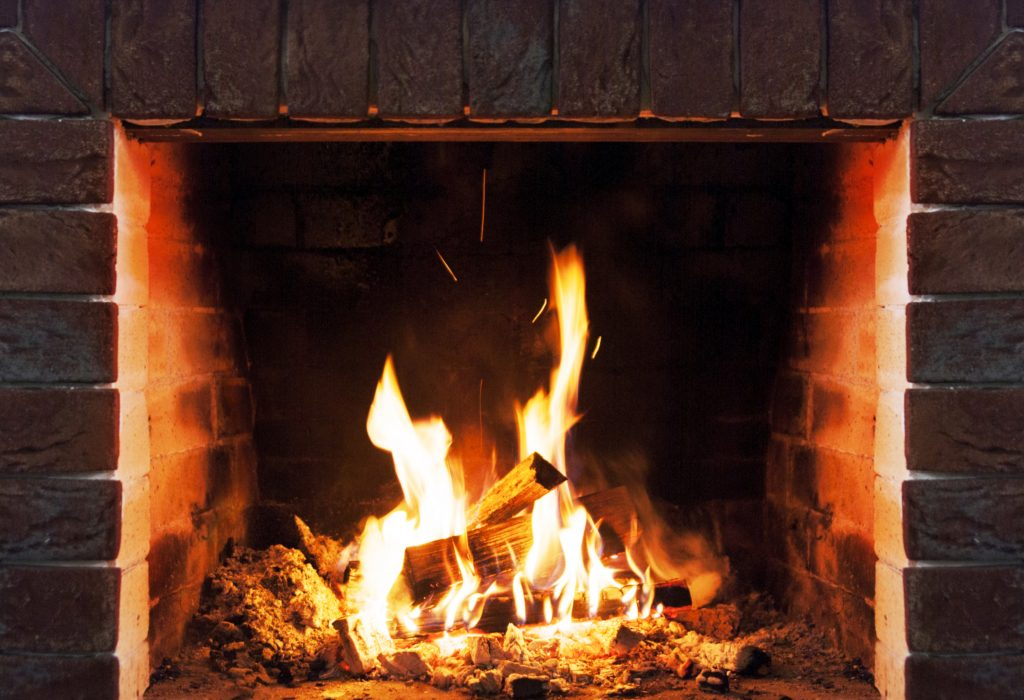 Close-up of wood logs and flames in a brick fireplace
