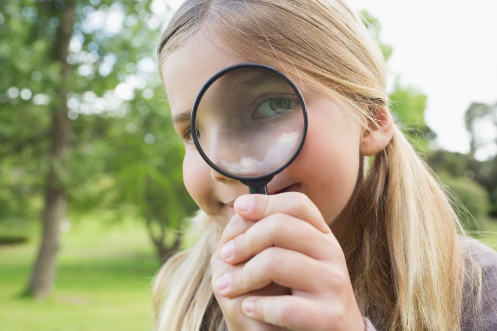 Close-up of a girl looking out of a magnifying glass