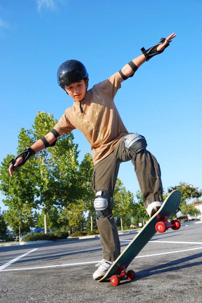 A boy does a skateboard trick while wearing a helmet and additional protective equipment