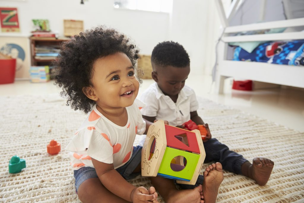 Close-up of a baby girl and boy playing with toys together