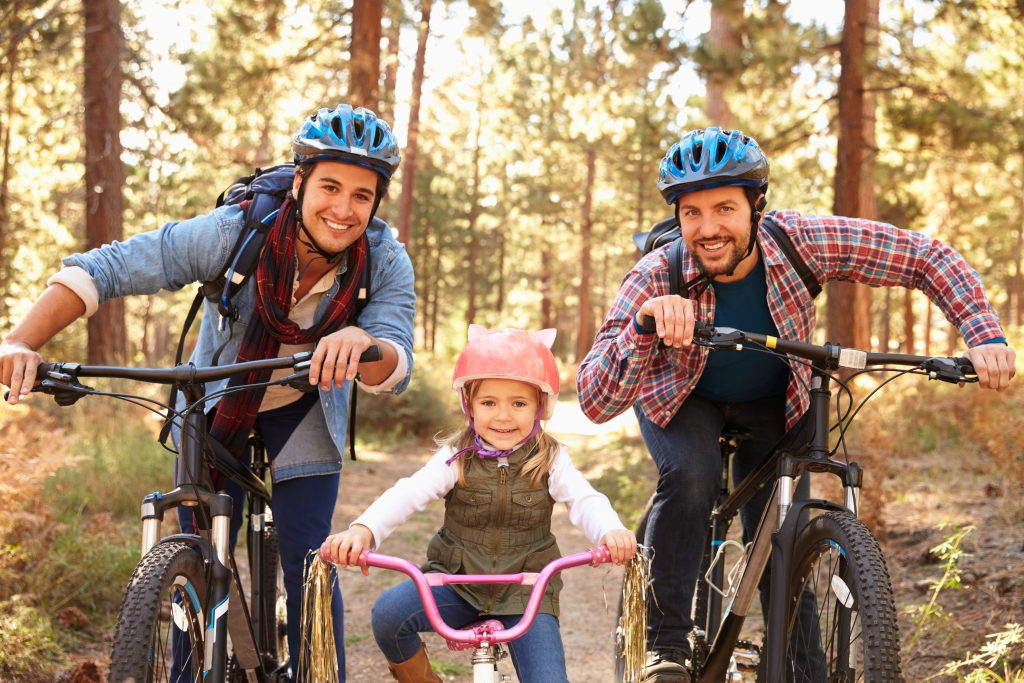 Male couple biking with child wearing helmets